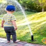 A toddler standing next to a water sprinkler irrigation system.
